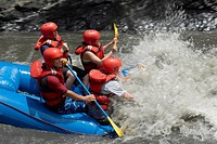 Side profile of four people rafting in a river