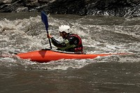 Side profile of a young man kayaking in a river