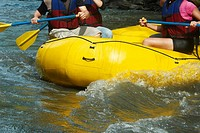 Mid section view of three people rafting in a river