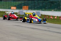 Two racecars racing on a motor racing track