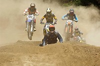 Five motocross riders riding motorcycles on a dirt road