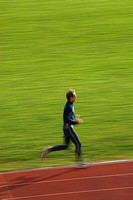 Side profile of a mid adult man running on a running track