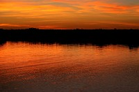 Orange glow of the sky in water at sunset, Okavango Delta, Botswana