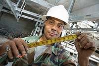 Portrait of a male construction worker holding a tape measure