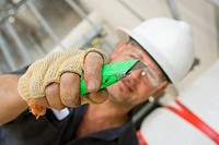 Close-up of a male construction worker holding a cutting tool (thumbnail)