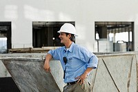 Side profile of an engineer leaning against an industrial equipment (thumbnail)