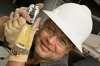 Close-up of a male construction worker holding a tape measure