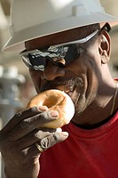 Mature man eating a bun