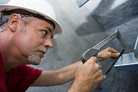 Close-up of a male construction worker cutting a metal sheet with a saw (thumbnail)