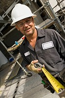 Portrait of a male construction worker holding a tape measure and smiling (thumbnail)