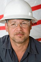 Portrait of a mature man with a pair of protective eyewear and a hardhat