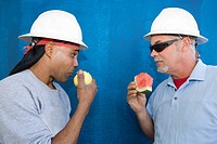 Close-up of two male construction workers face to face and eating fruits