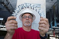 Close-up of a male construction worker folding a metal spring