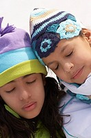 Close-up of two girls with their eyes closed