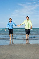 Mid adult couple walking on the beach with holding each others hands