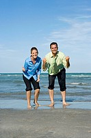 Mid adult couple clenching their fists on the beach (thumbnail)