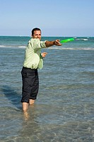 Mid adult man playing with a plastic disc on the beach