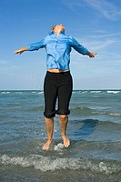 Mid adult woman jumping on the beach with her arms outstretched