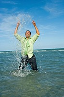 Mid adult man splashing water in the sea