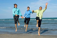 Two mid adult men with a mid adult woman holding each other's hands and jumping on the beach