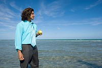 Mid adult man holding a green apple on the beach