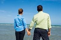 Rear view of a mid adult couple standing on the beach and holding hands
