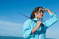 Mid adult man holding a fishing rod and looking away
