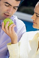Close-up of a businesswoman feeding a green apple to a businessman