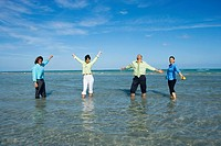 Two mid adult couples standing in water and looking cheerful