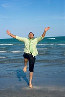Mid adult man standing on his one leg on the beach