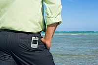 Mid section view of a man standing on the beach with his hands in his pockets