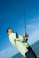 Side profile of a mid adult man holding a fishing rod on the beach