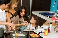 Mature woman standing with her two daughters and a maid smiling in the kitchen