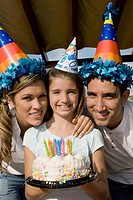 Portrait of a girl with her parents holding a birthday cake and smiling