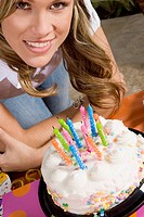 Portrait of a young woman standing in front of a birthday cake and smiling