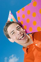Portrait of a boy holding a birthday present and laughing