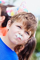 Close-up of a boy with a cake on his mouth