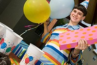 Portrait of a boy holding a birthday present and balloons (thumbnail)