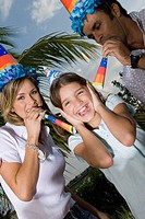 Portrait of a girl laughing with her parents blowing party horn blowers (thumbnail)