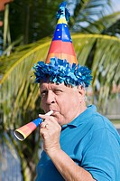 Side profile of a senior man blowing a party horn blower