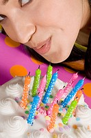 High angle view of a young woman blowing candles on a birthday cake