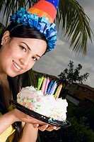 Portrait of a young woman holding a birthday cake and smiling