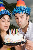 Close-up of a young woman with a mid adult man blowing candles on a birthday cake
