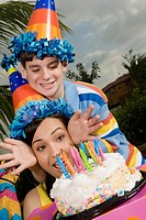 Young woman with her brother in front of a birthday cake