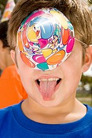 Close-up of a boy sticking her tongue out and covering his eyes with a birthday hat