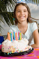Portrait of a girl smiling in front of a birthday cake