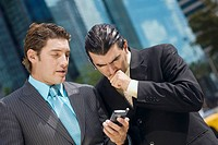 Two businessmen looking at a hand held device