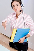Portrait of a businesswoman wearing a headset and carrying files