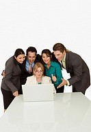 Businesswoman working on a laptop with four business executives standing beside her