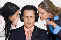 Close-up of a businessman listening to music while two businesswomen bothering him